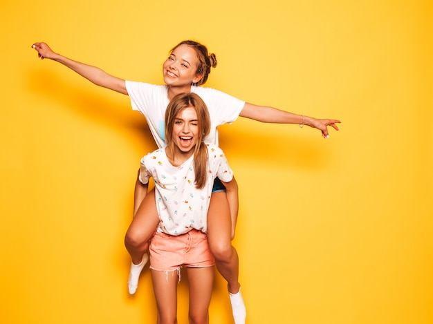 Two young beautiful smiling hipster girls in trendy summer clothes. sexy carefree women posing near yellow wall.model sitting on her friend's back and raising hands
