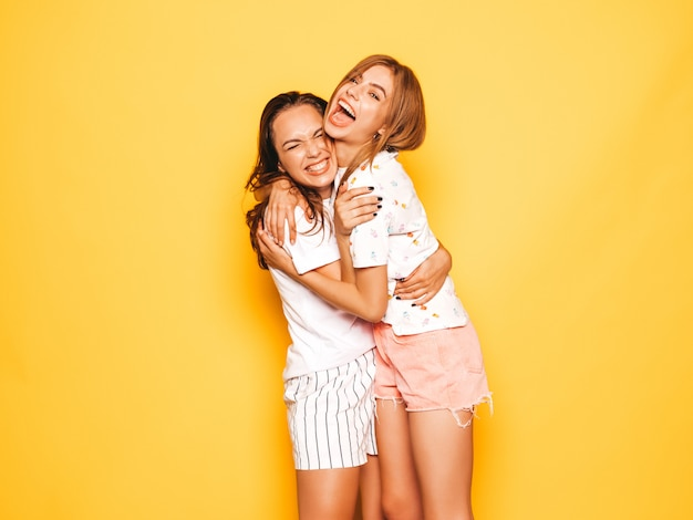 Two young beautiful smiling hipster girls in trendy summer clothes. sexy carefree women posing near yellow wall. positive models going crazy and having fun.hugging