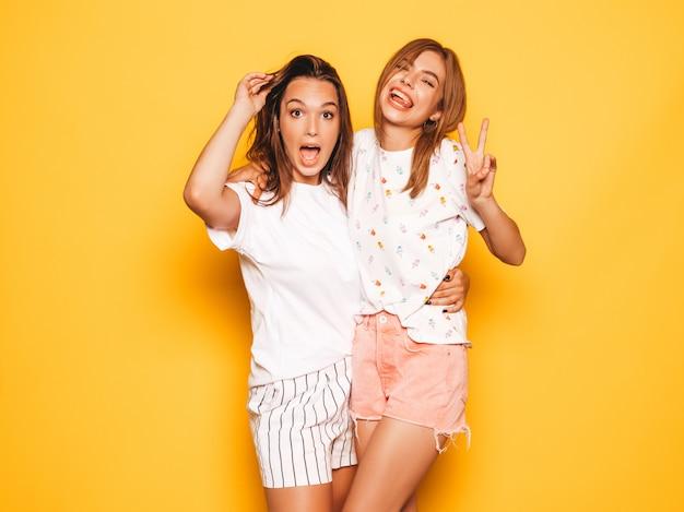 Due giovani belle ragazze sorridenti hipster in abiti estivi alla moda. donne spensierate sexy che posano vicino alla parete gialla. modelle positive che impazziscono e si divertono