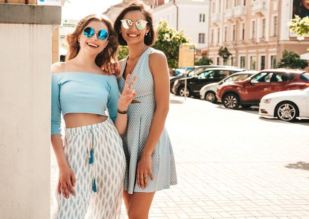 Due giovani belle ragazze sorridenti dei pantaloni a vita bassa in vestiti d'avanguardia di estate donne spensierate sexy che posano sul fondo della via in occhiali da sole. modelli positivi che si divertono e si abbracciano Foto Gratuite