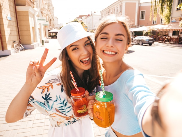 Two young beautiful smiling hipster girls in trendy summer clothes