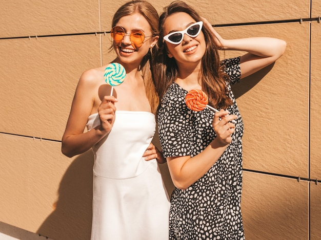 Two young beautiful smiling hipster girls in trendy summer dress.