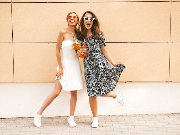 Two young beautiful smiling hipster girls in trendy summer dresses.