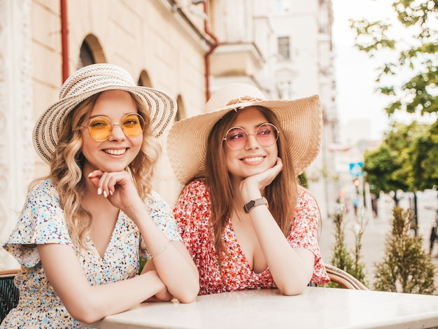 Two young beautiful smiling hipster girls in trendy summer sundress.carefree women chatting in veranda cafe on the street background in sunglasses.positive models having fun and communicating