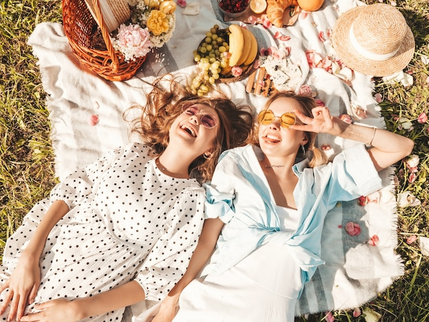 Two young beautiful smiling hipster girls in trendy summer sundress and hats.carefree women making picnic outside.