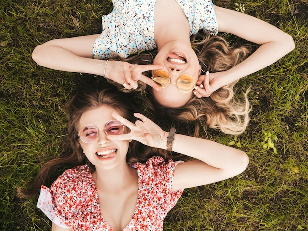 Two young beautiful smiling hipster girls in trendy summer sundress.sexy carefree women lying on the green grass in sunglasses.positive models having fun.top view.they show peace sign