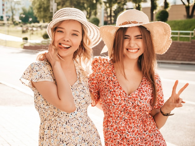 Two young beautiful smiling hipster girls in trendy summer sundress.sexy carefree women posing on the street background in hats. positive models having fun and hugging.they show peace sign and tongue Free Photo
