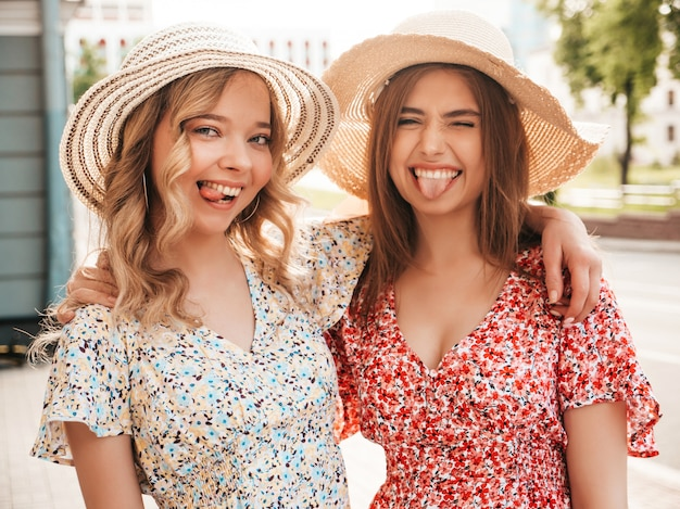 Two young beautiful smiling hipster girls in trendy summer sundress.sexy carefree women posing on street background in hats. positive models having fun and hugging.they show tongues