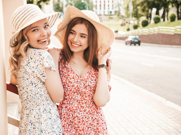 Two young beautiful smiling hipster girls in trendy summer sundress.sexy carefree women posing on street background in hats. positive models having fun and hugging