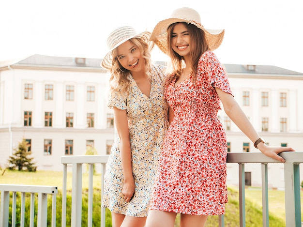 Two young beautiful smiling hipster girls in trendy summer sundress.sexy carefree women posing on the street background in hats. positive models having fun and hugging