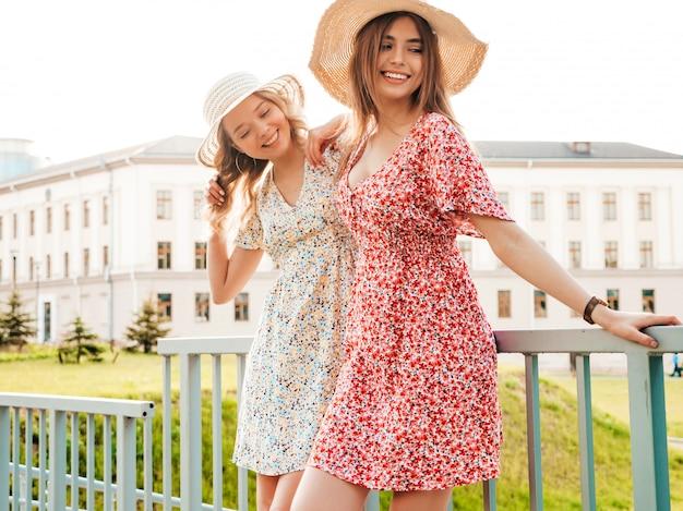 Due giovani belle ragazze sorridenti dei pantaloni a vita bassa nelle prendisole estive d'avanguardia donne spensierate sexy che posano sui precedenti della via in cappelli. modelli positivi che si divertono e si abbracciano