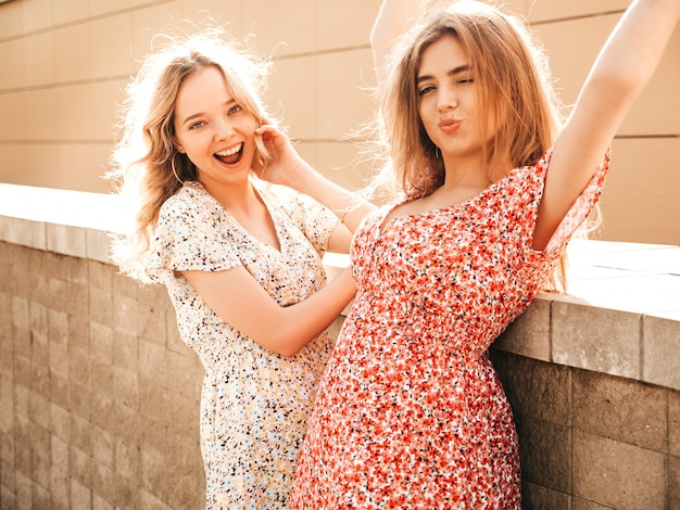 Two young beautiful smiling hipster girls in trendy summer sundress.sexy carefree women posing on the street background. positive models having fun and going crazy