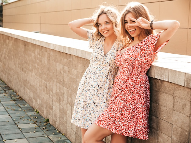 Two young beautiful smiling hipster girls in trendy summer sundress.sexy carefree women posing on the street background. positive models having fun and show peace sign