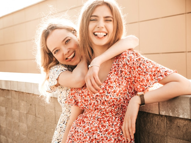 Two young beautiful smiling hipster girls in trendy summer sundress.sexy carefree women posing on the street background. positive models having fun and show tongues