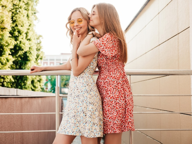 Two young beautiful smiling hipster girls in trendy summer sundress.sexy carefree women posing on the street background in sunglasses. positive models having fun and going crazy