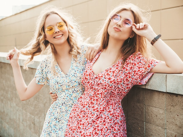 Two young beautiful smiling hipster girls in trendy summer sundress.sexy carefree women posing on the street background in sunglasses. positive models having fun and hugging