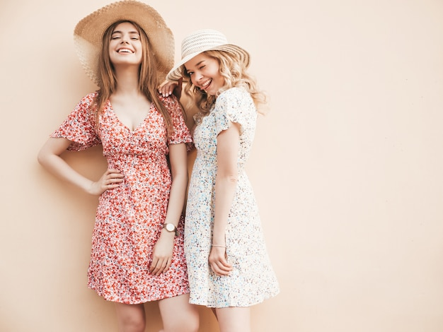 Two young beautiful smiling hipster girls in trendy summer sundress.sexy carefree women posing on the street near wall in hats. positive models having fun and hugging