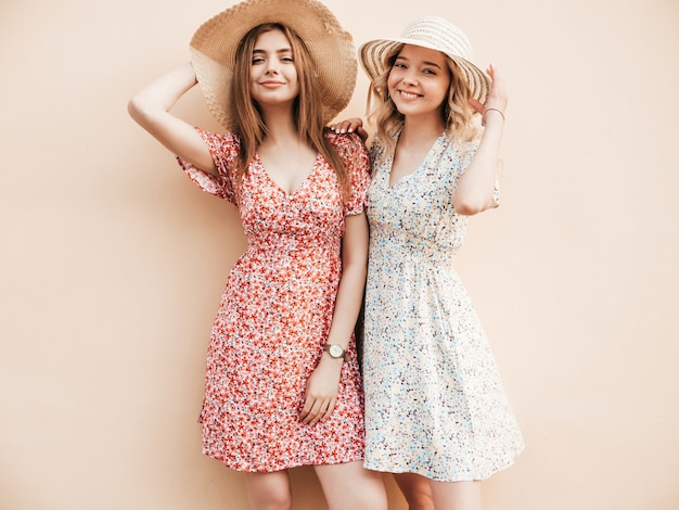Due giovani belle ragazze sorridenti dei pantaloni a vita bassa in prendisole estive d'avanguardia donne sexy spensierate che posano sulla via vicino alla parete in cappelli. modelli positivi che si divertono e si abbracciano