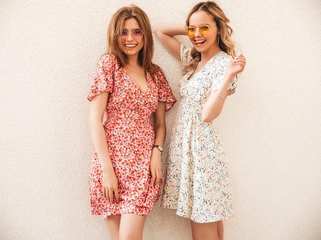 Due giovani belle ragazze sorridenti dei pantaloni a vita bassa in prendisole estive d'avanguardia donne sexy spensierate che posano nella via vicino alla parete in occhiali da sole. modelle positive che si divertono e impazziscono