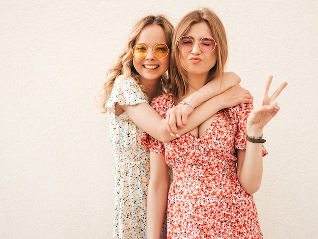 Two young beautiful smiling hipster girls in trendy summer sundress.sexy carefree women posing in the street near wall in sunglasses. positive models having fun and show peace sign