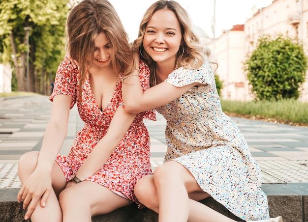 Due giovani belle ragazze sorridenti dei pantaloni a vita bassa nelle prendisole d'avanguardia di estate. donne spensierate sexy che si siedono sui precedenti della via. modelle positive che si divertono e si abbracciano. impazziscono