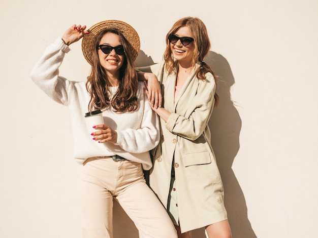 Two young beautiful smiling hipster girls in trendy white sweater and coat