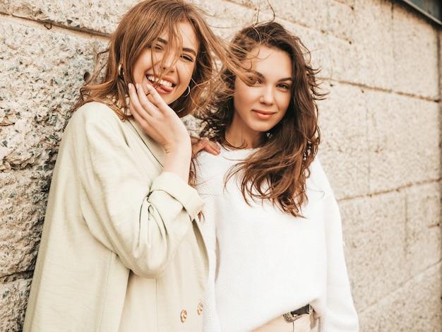 Due giovani belle ragazze hipster sorridenti in maglione e cappotto bianchi alla moda