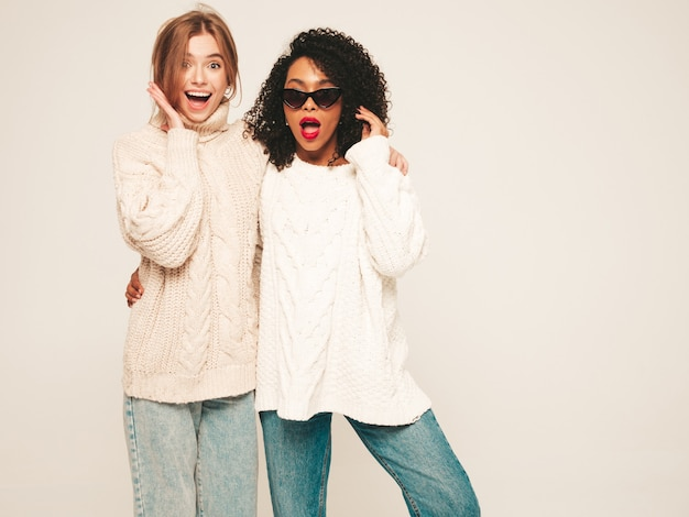 Two young beautiful smiling hipster girls in trendy winter sweaters. positive models having fun and hugging