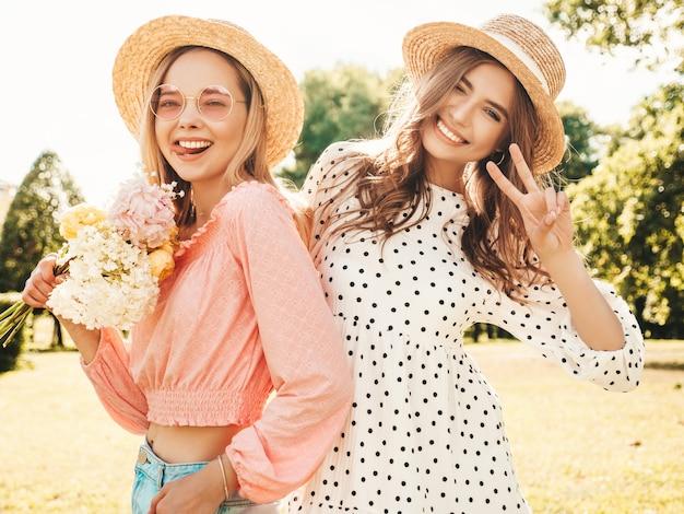 トレンディな夏のサンドレスで2人の若い美しい笑顔の流行に敏感な女性。帽子をかぶって公園でポーズをとるセクシーな屈託のない女性。