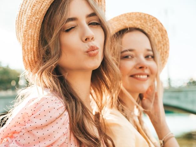 Две молодые красивые улыбающиеся хипстерские женщины в модном летнем сарафане