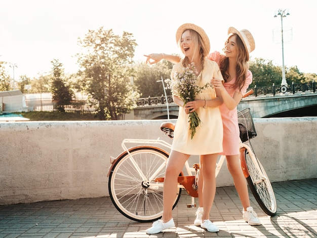Two young beautiful smiling hipster woman in trendy summer sundress embankment in hats