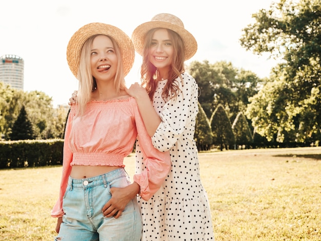 Two young beautiful smiling hipster woman in trendy summer sundress. sexy carefree women posing in the park in hats.