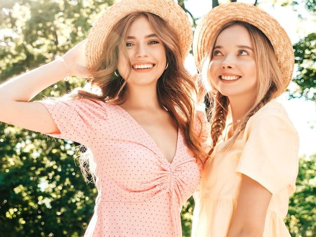 Due giovani belle donne sorridenti hipster in prendisole estive alla moda