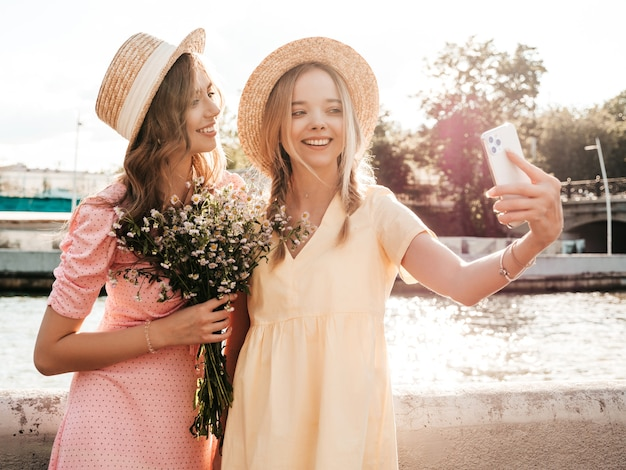 Two young beautiful smiling hipster woman in trendy summer sundress