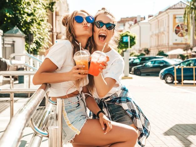 Две молодые красивые улыбающиеся хипстерские женщины в модной летней одежде