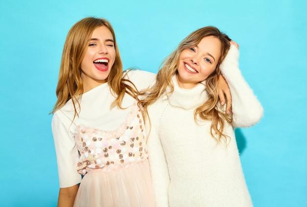 トレンディな夏の白い服の2人の若い美しい笑顔流行に敏感な女性。セクシーな屈託のない女性が青い壁の近くでポーズします。ポジティブモデル