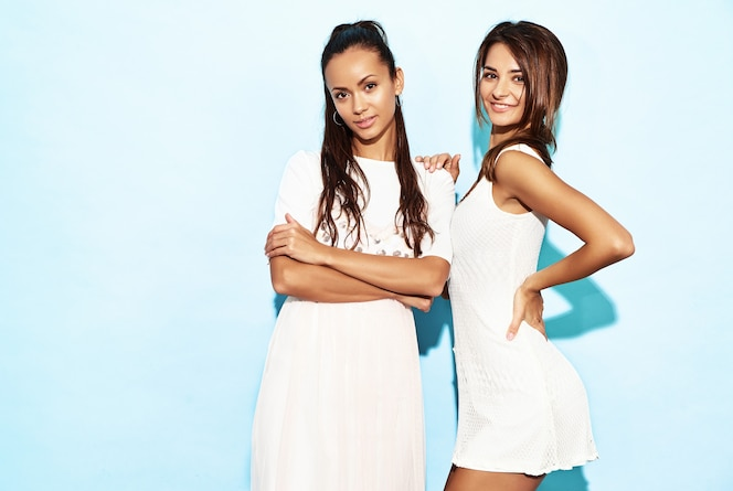 Two young beautiful smiling hipster women in trendy summer clothes. sexy carefree women posing near blue wall. positive models