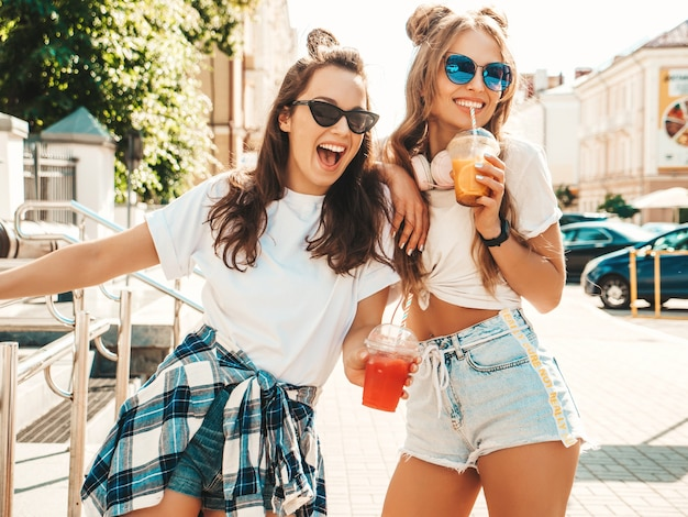 Two young beautiful smiling hipster women in trendy summer clothes