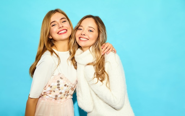 Two young beautiful smiling hipster women in trendy summer white clothes. sexy carefree women posing near blue wall. positive models