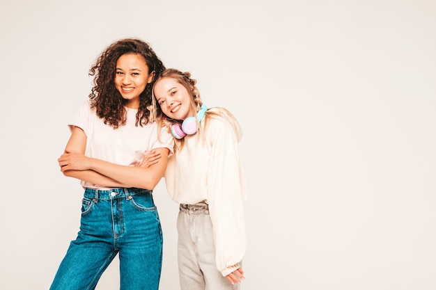 Two young beautiful smiling international hipster female in trendy summer clothes. carefree women posing on grey