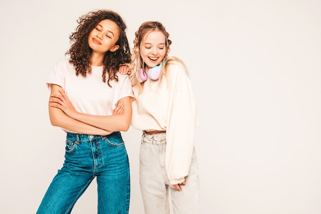 Two young beautiful smiling international hipster female in trendy summer clothes. carefree women posing in studio