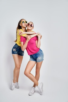 Two young beautiful smiling international hipster female in trendy summer clothes carefree women posing on white background in studio