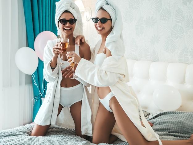 흰 목욕 가운과 머리에 수건을 입은 두 젊은 아름다운 웃는 여성