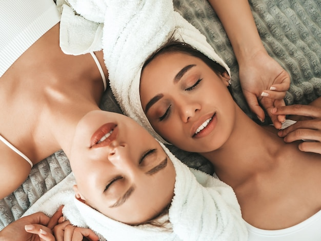 頭に白いバスローブとタオルで2人の若い美しい笑顔の女性