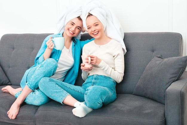 ソファに座っている2人の若い美しい笑顔の女性。高級マンションやホテルの部屋で屋内でポーズをとるのんきなモデル。彼らは自宅で美容トリートメントをしています