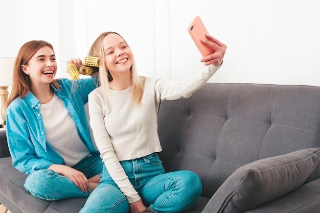 ソファに座っている2人の若い美しい笑顔の女性。高級マンションやホテルの部屋で屋内でポーズをとるのんきなモデル