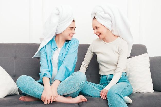 Две молодые красивые улыбающиеся женщины, сидящие на диване