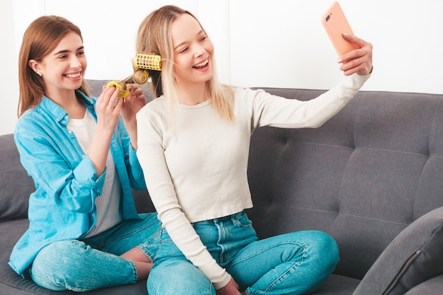 Two young beautiful smiling women sitting at the sofa. carefree models posing indoors in posh apartment or hotel room