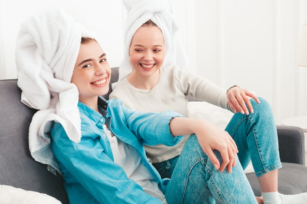 Two young beautiful smiling women sitting at the sofa