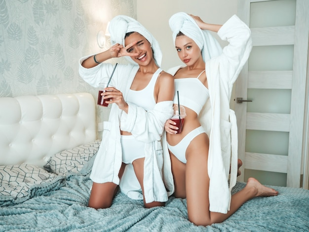 Two young beautiful smiling women in white bathrobes and towels on head. sexy carefree models sitting on bed in posh apartment or hotel room. they drinking fresh cocktail smoothie